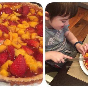 Sebastian cutting his strawberry and mango tart