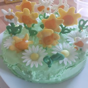 Cake iced green with yellow and white iced flowers