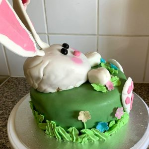 Side view of green cake with a while rabbit coming out of it