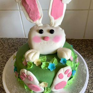 Green cake with a while rabbit coming out of it